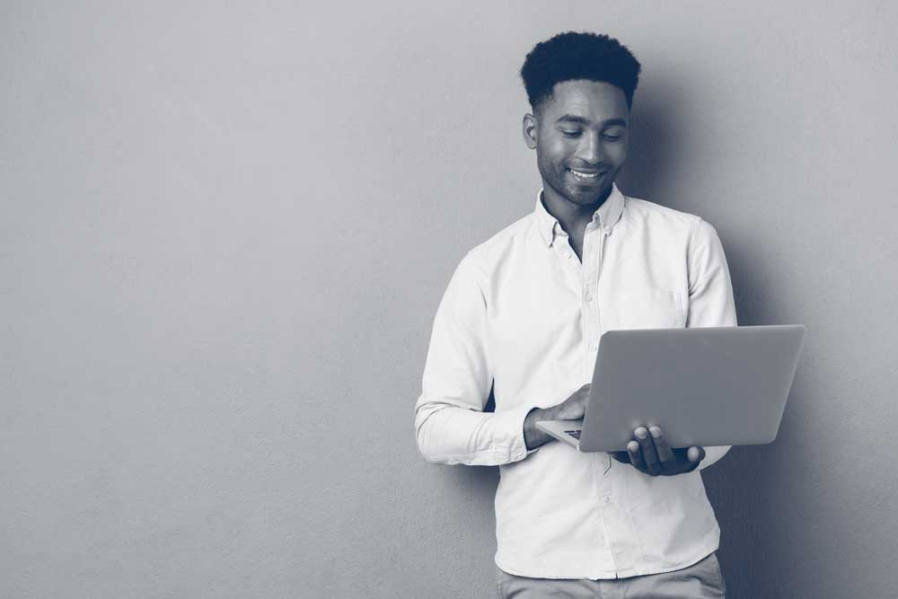 young black man working on laptop