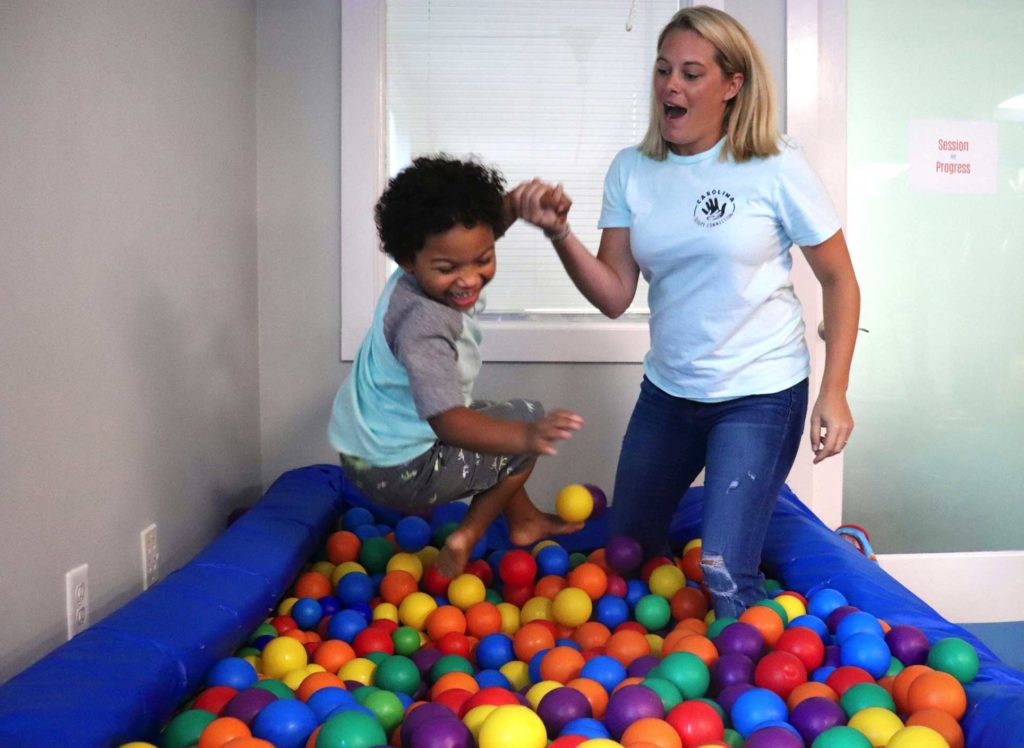 Young boy in ballpit with staff member of CTC